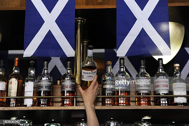 A barman lifts a bottle of Scotch whisky from a shelf in the Deoch An Dorus pub in the Partick area of Glasgow on September 17 2013 Murals in the...
