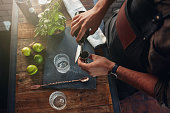 Close up of barman hands pouring alcoholic drink in to a jigger to prepare a cocktail, with basil leaves and lemons on the bar counter.