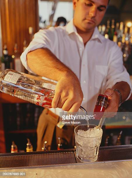 Barman mixing drink on bar counter
