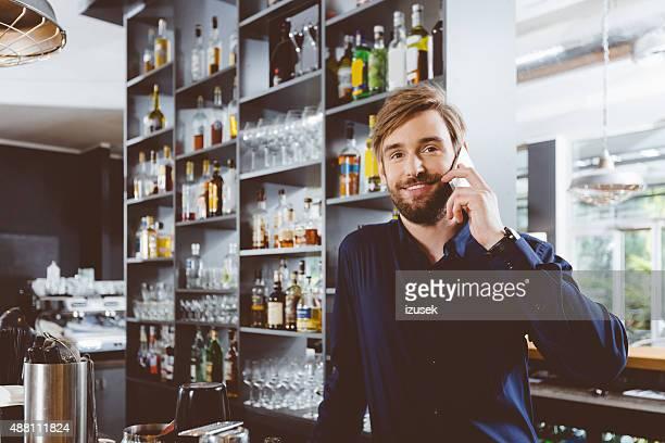 Barman sur le téléphone dans la pub