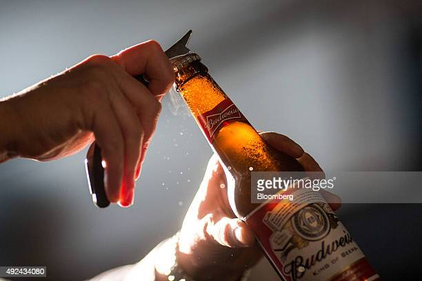 A barman opens a bottle of Budweiser beer brewed by AnheuserBusch InBev NV in The Capitol a JD Wetherspoons Plc public house in this arranged...