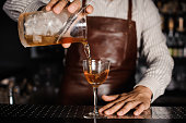 barman making and pouring alcoholic cocktail at the bar