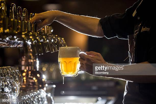 A barman pours a glass of beer from a tap in the restaurant at the Pilsner Urquell brewery operated by SABMiller Plc in Plzen Czech Republic on...