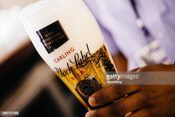 A barman pours a glass of Carling Black Label beer in the SABMiller Plc brewhouse in the Sandton district of Johannesburg South Africa on Monday Aug...