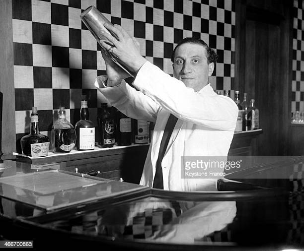 Barman preparing a cocktail with a shaker in November 1929 in Paris France