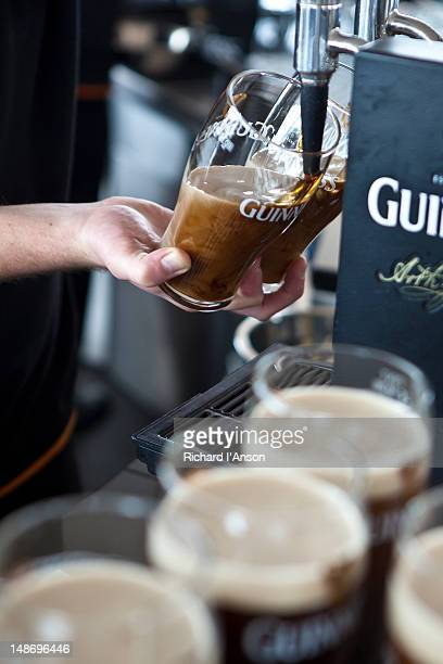 Barman pulling pints of Guinness at Gravity Bar at Guinness Storehouse.