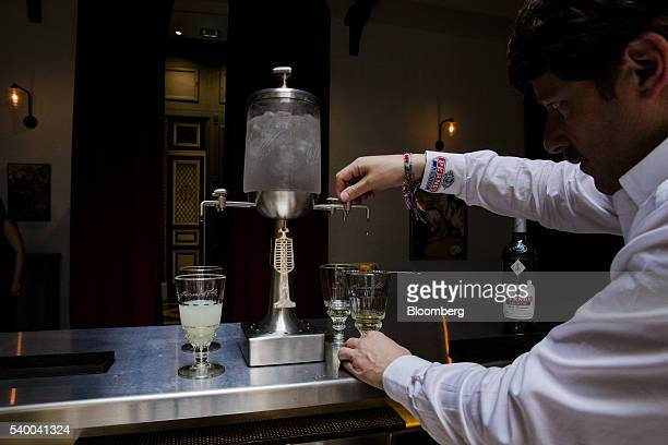 A barman releases drops of chilled water from a fountain into a pontarlier glass of absinthe in the bar area at Pernod Ricard SA's absinthe...