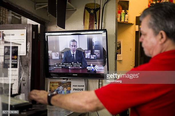 A barman serves a customer as Alejandro Garcia Padilla governor of Puerto Rico is seen giving a speech on a television screen in a bar in San Juan...