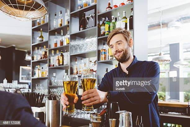 Barman che serve birra in un pub