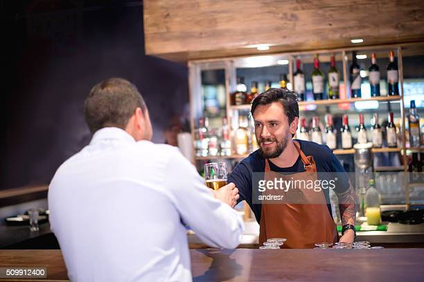 Barman serving drink to a man at the bar