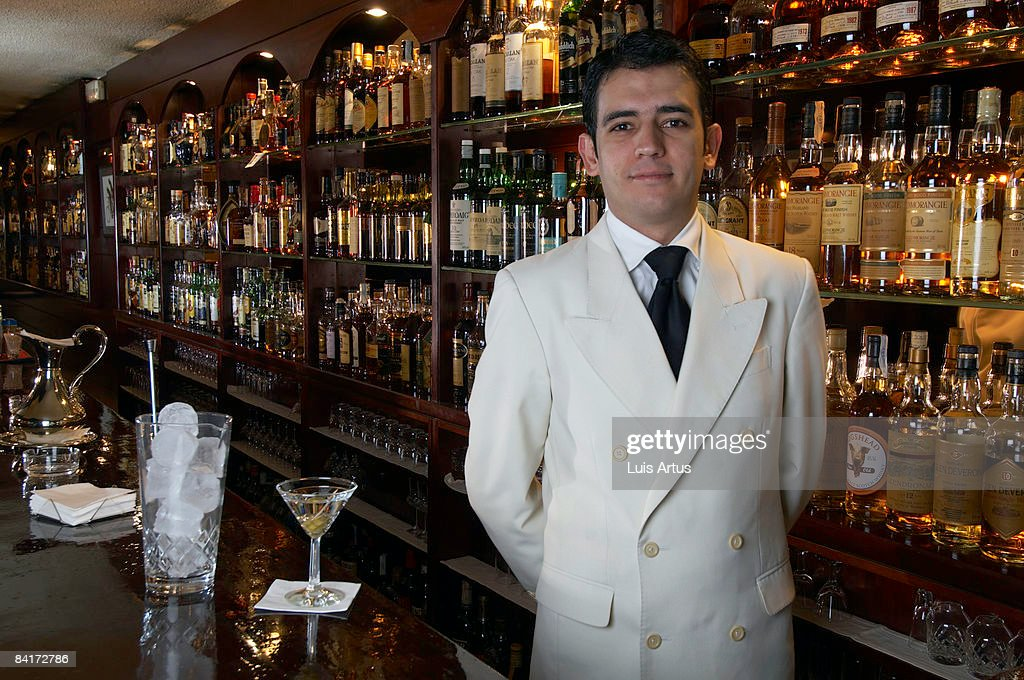 Barman stands at bar with drink : Stock Photo