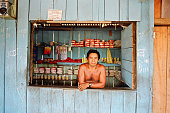 A barman stands at the hatch of his bar which doubles as a village shop The Floresta Nacional do Tapajos a 6500 km2 protected reserve was home to...