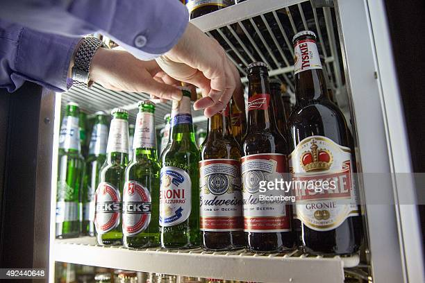 A barman takes a bottle of Budweiser beer brewed by AnheuserBusch InBev NV right and a bottle of Peroni beer brewed by SABMiller Plc from a fridge in...