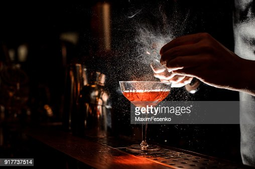 Barmans hands sprinkling the juice into the cocktail glass : Stock Photo