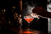 Barmans hands sprinkling the juice into the cocktail glass filled with alcoholic drink on the dark background