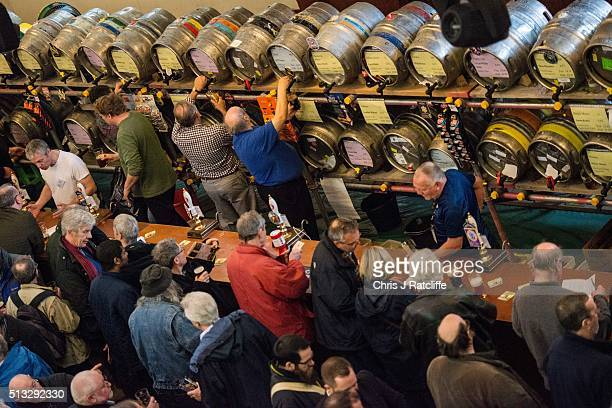 Barmen pour ales and stouts for drinkers at the London Drinker Beer and Cider Festival at the Camden Centre on March 2 2016 in London England The...