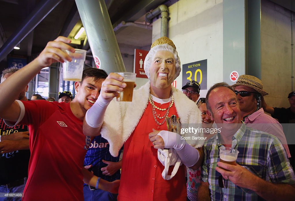 A Barmy Army member dressed as Queen Elizabeth II drinks a beer during day one of the First Ashes Test match between Australia and England at The Gabba on November 21, 2013 in Brisbane, Australia. The Barmy Army is a group of English cricket fans which arranges touring parties for some of its members to support the English cricket team on overseas tours, as well as followers of the team who join in with match day activities in the crowd, but do not travel as part of an organised tour.