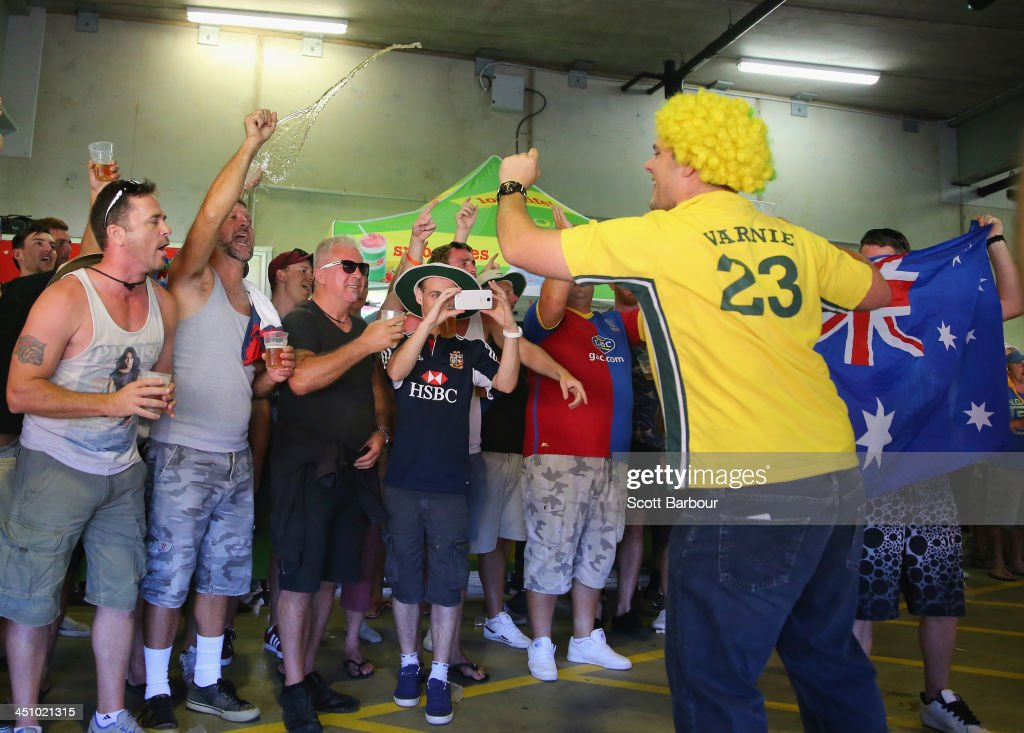 A Barmy Army member throws beer as an Australian supporter sings during day one of the First Ashes Test match between Australia and England at The Gabba on November 21, 2013 in Brisbane, Australia. The Barmy Army is a group of English cricket fans which arranges touring parties for some of its members to support the English cricket team on overseas tours, as well as followers of the team who join in with match day activities in the crowd, but do not travel as part of an organised tour.