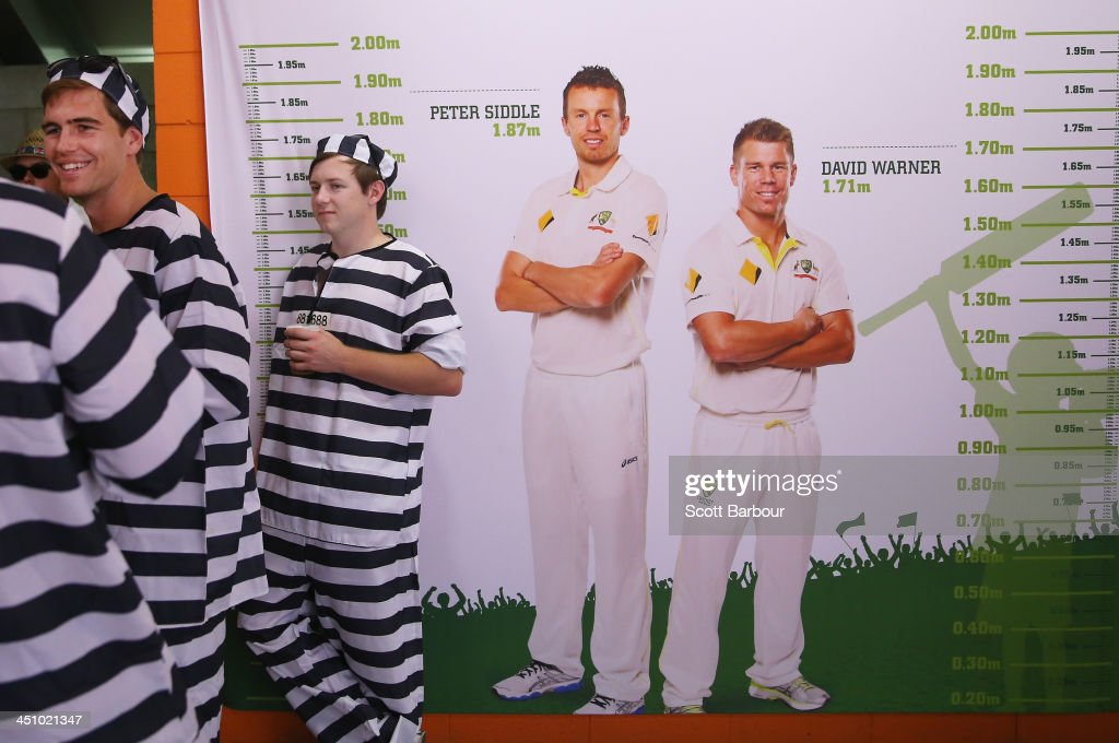 Barmy Army members dressed as convicts wait for play to start next to photographs of Australian cricketers during day one of the First Ashes Test match between Australia and England at The Gabba on November 21, 2013 in Brisbane, Australia. The Barmy Army is a group of English cricket fans which arranges touring parties for some of its members to support the English cricket team on overseas tours, as well as followers of the team who join in with match day activities in the crowd, but do not travel as part of an organised tour.