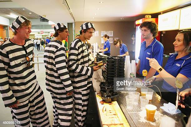 Barmy Army members dressed as convicts wait in line to purchase beer during day one of the First Ashes Test match between Australia and England at...