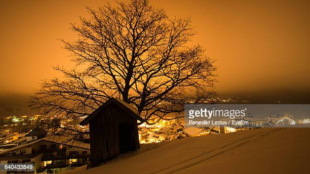 Barn By Silhouette Bare Tree On Snow Covered Field By Illuminated Town During Sunset
