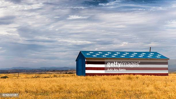 Barn in field painted with stars and stripes, California, USA