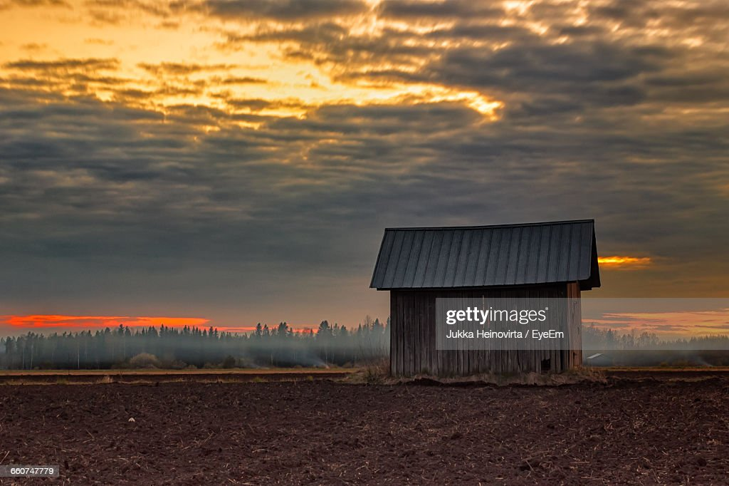 Barn On Agricultural Field Against Cloudy Sky During Sunset