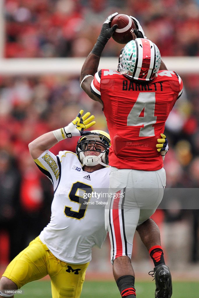 C.J. Barnett #4 of the Ohio State Buckeyes intercepts a pass intended for Drew Dileo #9 of the Michigan Wolverines in the fourth quarter to seal the win for Ohio State at Ohio Stadium on November 24, 2012 in Columbus, Ohio. Ohio State defeated Michigan 26-21.