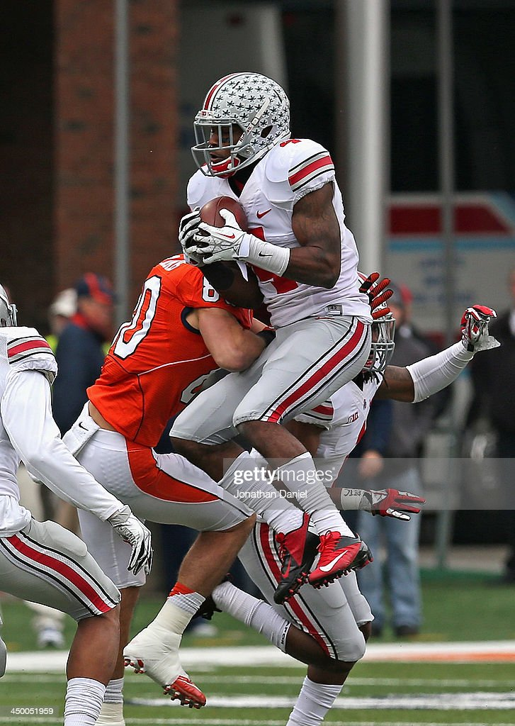 C.J. Barnett #4 of the Ohio State Buckeyes leaps over Spencer Harris #80 of the Illinois Fighting Illini to intercept a pass at Memorial Stadium on November 16, 2013 in Champaign, Illinois.