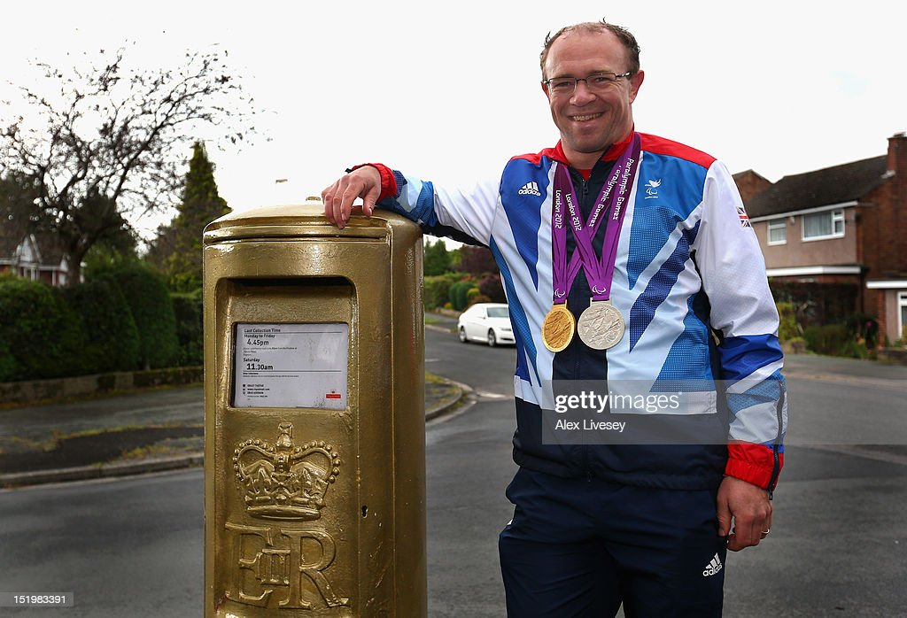 Barney Storey poses with his Paralympic medals next to a gold painted Royal Mail post box in the village of Poynton on September 14, 2012 in Stockport, England.