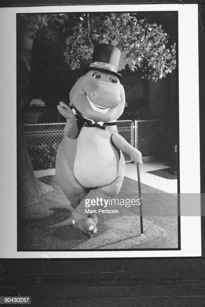 Barney the dinosaur wearing top hat bow tie holding cane while performing song dance on the TV show Barney And Friends