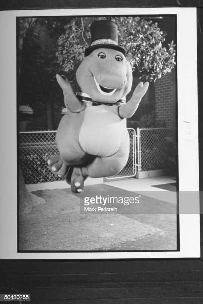 Barney the dinosaur wearing top hat bow tie jumping in the air while performing song dance on the TV show Barney And Friends