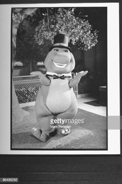 Barney the dinosaur wearing top hat bow tie performing song dance on the TV show Barney And Friends