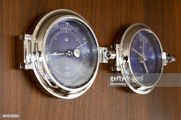 A barometer and clock hang on a wall of a Princess 56 motor yacht manufactured by Princess Yachts International Plc at the Singapore Yacht Show in...