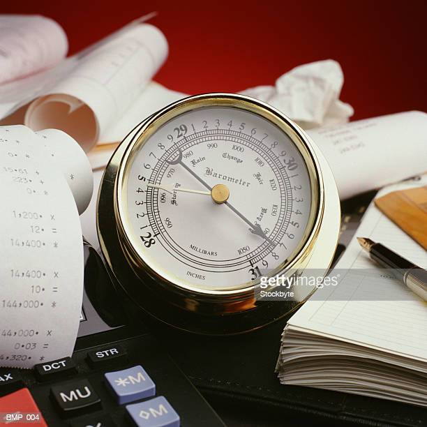 Barometer on desktop, surrounded by paper, calculator and pen