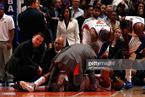 Baron Davis of the New York Knicks is tended to by the team medical staff as players Carmelo Anthony and Amare Stoudemire after Davis injured his...