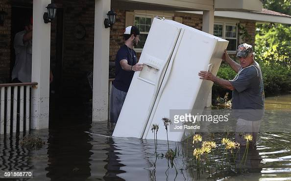 Baron Leblanc and George Snyder move a refrigerator out of George's flooded home on August 18 2016 in St Amant Louisiana Last week Louisiana was...
