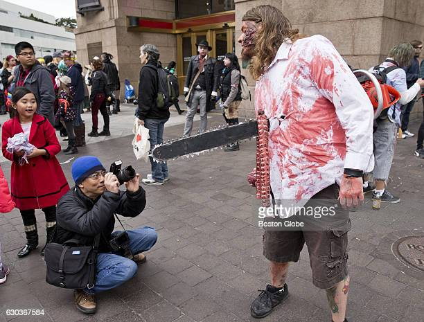 Baron Loke of Danvers takes a picture of zombie Tommy Ryan of Mansfield before the start of the zombie march in front of South Station in Boston on...