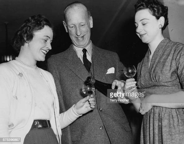 Baron Van Canstein representing the West German Ministry of Agriculture pouring a glass of wine for London ladies Thelma Scott and Daphne Alexander...