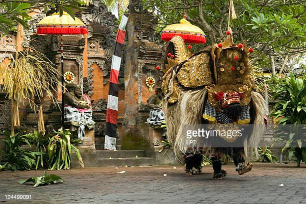 Barong dance in Bali, Indonesia next to tropical foliage