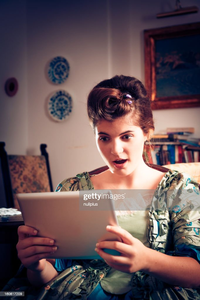 baroque lady is amazed with the new tablet computers : Stock Photo