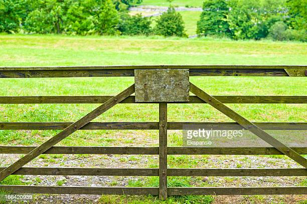 Barred Wooden Gate with Blank Sign in Green Field
