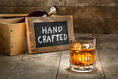 Barrel aged craft liquor spirits glass ice bourbon whisky scotch brandy rum on wood bar table Hand crafted small batch with sign