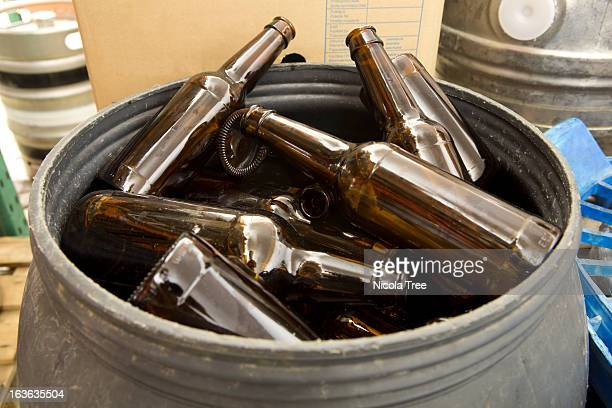 A barrel full of empty glass bottles in a brewery