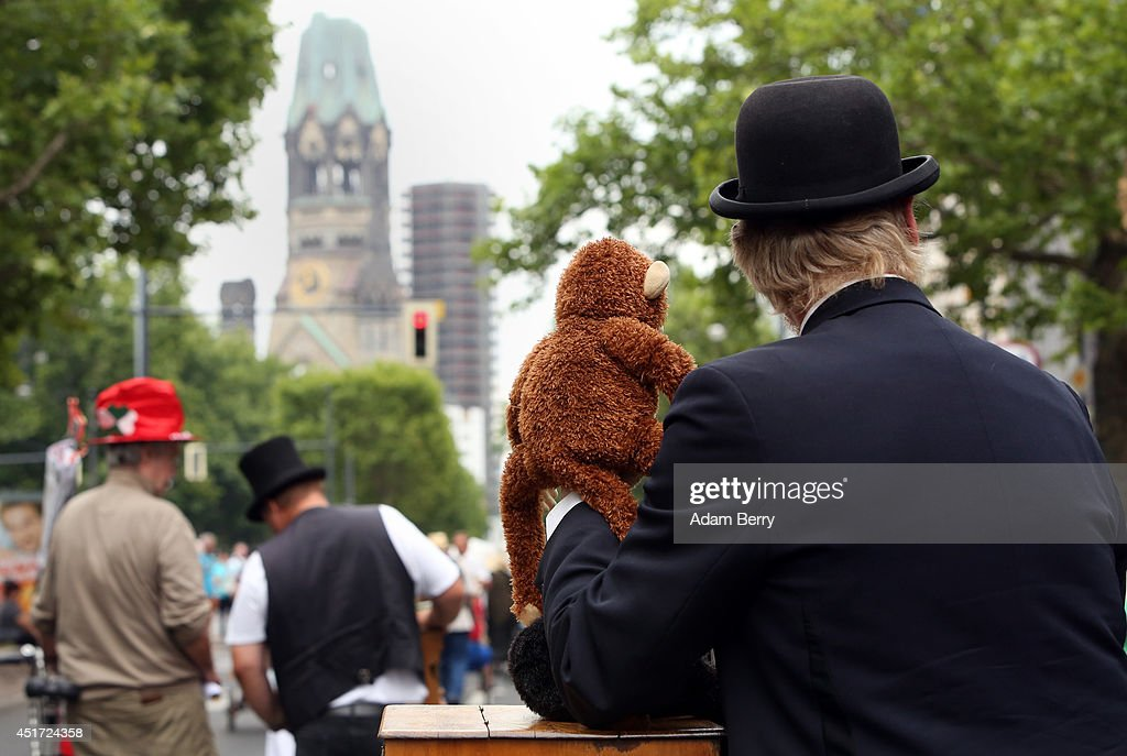 A barrel organ player performs with a stuffed toy monkey in front of the Kaiser Wilhelm Memorial Church in a parade during the 34th International...