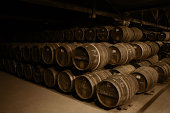 Rows of barrels stacked on top of each other in a dark cellar.