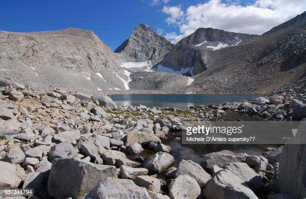 Barren alpine landscape with jagged peak and a lake
