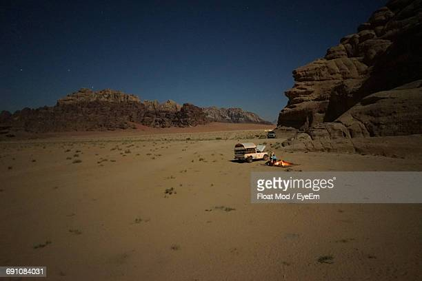 Barren Landscape With Vehicle And Fire By Rocky Cliff Against Clear Sky