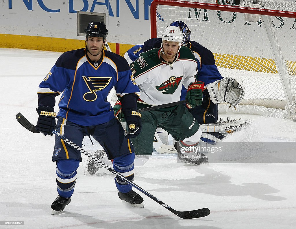 Barret Jackman #5 of the St. Louis Blues skates against Kyle Brodziak #21 of the Minnesota Wild in an NHL game on January 27, 2013 at Scottrade Center in St. Louis, Missouri.