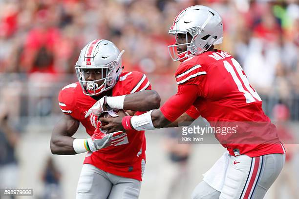 T Barrett of the Ohio State Buckeyes hands the ball off to Curtis Samuel of the Ohio State Buckeyes during the first quarter of the game against the...